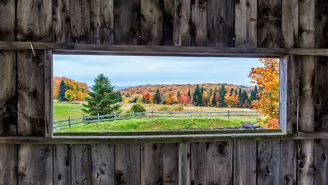 The scenic Vermont fall foliage is framed within the view out of the side window of Fosters Covered Bridge in Cabot.