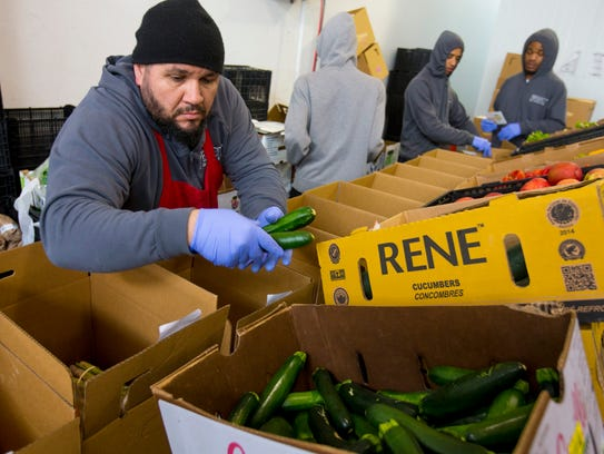 """Imperfect Produce operation associate, Brutus Oliverira, assembles boxes of """"ugly"""" fruits and vegetables. The San Francisco company then delivers the produce to your home. The saving of purchasing these imperfect produce can be 25-50 percent off prices at the grocery store."""