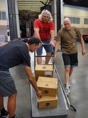 Joe Howard, left, Sam Montag and Blaise Mikulewicz of Richardson Bike Mart unload merchandise for their vendor booths at the Ray Clymer Exhibit Hall Wednesday afternoon.