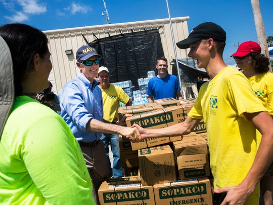 Gov. Rick Scott shakes hands with volunteers from The Church of Jesus Christ of Latter-day Saints outside of the Everglades City Fire Department while touring the area on Sunday, Sept. 17, 2017.