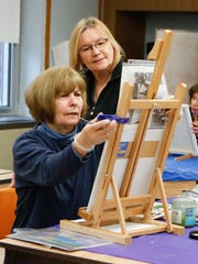 Art instructor Gwynn Guerriero, back work with Loretta Malovanoi from Ramapo on her painting at the Clarkstown Learning Center in Congers on Friday, March 31, 2017.