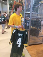 Brett Favre, 18, of Omaha, Neb., holds a jersey for former Green Bay Packers great Brett Favre in the Packers Pro Shop at Lambeau Field on Wednesday, July 15. The younger Favre is spending the week in Green Bay for a mission trip with fellow teens and adult chaperones from his church in Omaha.