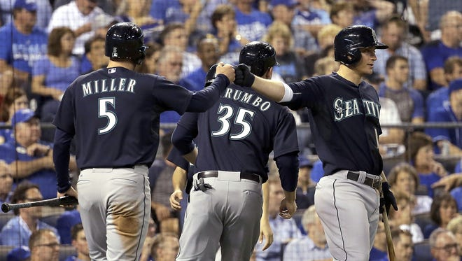 Seattle Mariners' Brad Miller (5) celebrates with Kyle Seager, right, after Miller and Mark Trumbo (35) scored on a triple hit by Ketel Marte during the fifth inning of a baseball game against the Kansas City Royals on Wednesday, Sept. 23, 2015, in Kansas City, Mo.