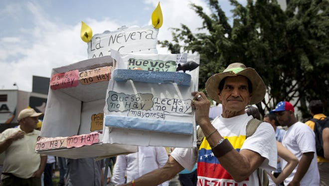 A man holds a model of an empty refrigerator to protest food shortages in Caracas, Venezuela, on May 14, 2016.