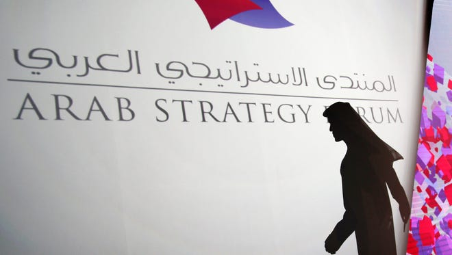 Shadow of an Emirati official casts on the logo of the Arab Strategy Forum during the opening day in Dubai, United Arab Emirates, Sunday, Dec. 14, 2014. The secretary-general of OPEC, Abdullah al-Badri, is urging Gulf Arab nations to continue investing in oilfield development despite the sharp slide in crude prices.