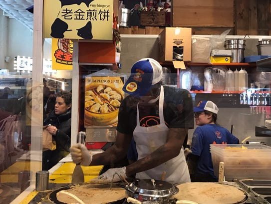 A line cook at Mr Bing's food stall inside of Urbanspace