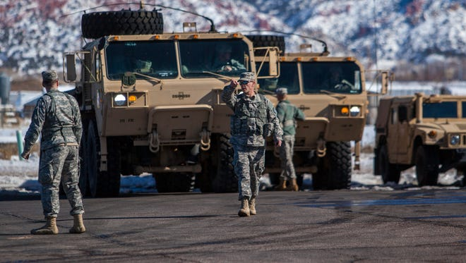 A soldier with the 213th Forward Support Company leads a vehicle out of the parking lot of the Utah National Guard Armory in Cedar City, Friday, Feb. 6, 2016.