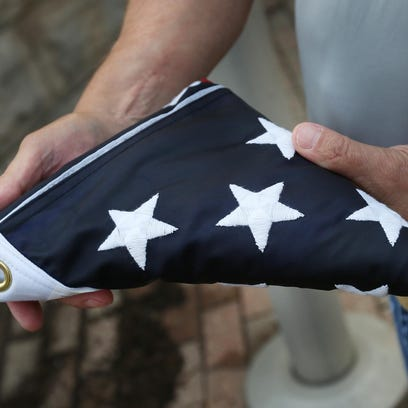 Steve Stiegelmeyer holds a folded American flag brought