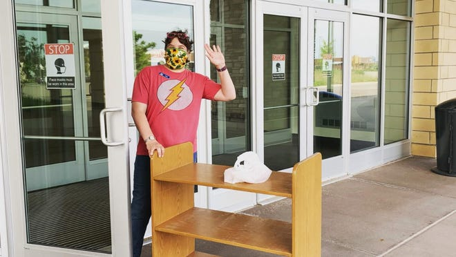 A staff member poses for a photo at Herrick District Library North Branch, currently located in The Shops at Westshore. The branch is now open for grab-and-go service inside the building.