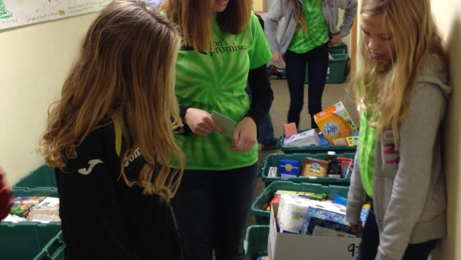 Peyton Medick, center, the founder of Peyton's Promise, instructs twin sisters Lauren, left, and Jordyn Langbehn on how to sort donated food.
