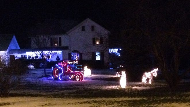 An illuminated tractor on East Shore Drive in Lansing.