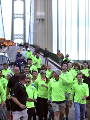 Michigan Gov. Rick Snyder, center, waves as he walks the five-mile-long Mackinac Bridge Monday, Sept. 2, 2013 during the annual Labor Day Bridge Walk in Mackinaw City, Mich.