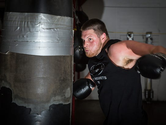 Eric Kuznar trains with a heavy bag at the Muncie Pal