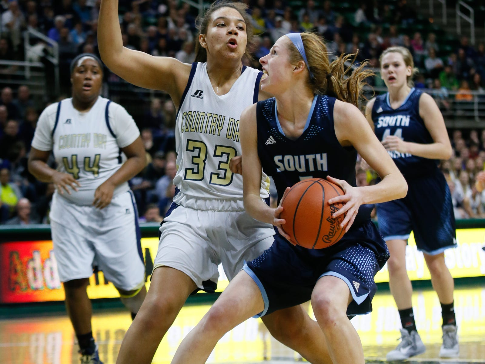 Grand Rapids South Christian's Mariel Bruxvoort goes hard towards the basket against Birmingham Detroit Country Day's Destiny Pitts during South Christian's 57-46 win in the Class B state semifinal Friday in East Lansing.