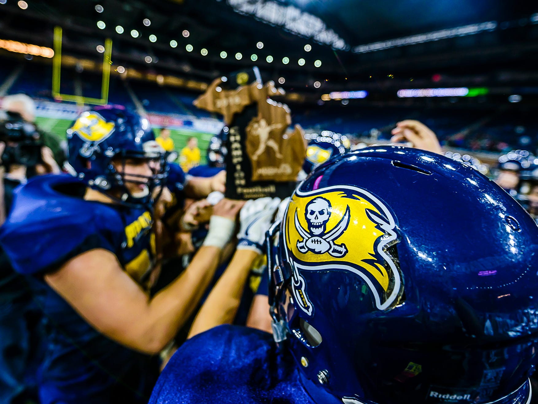The Pewamo-Westphalia football team holds the Division 7 state championship trophy after defeating Detroit Loyola Saturday November 26, 2016 at Ford Field in Detroit.