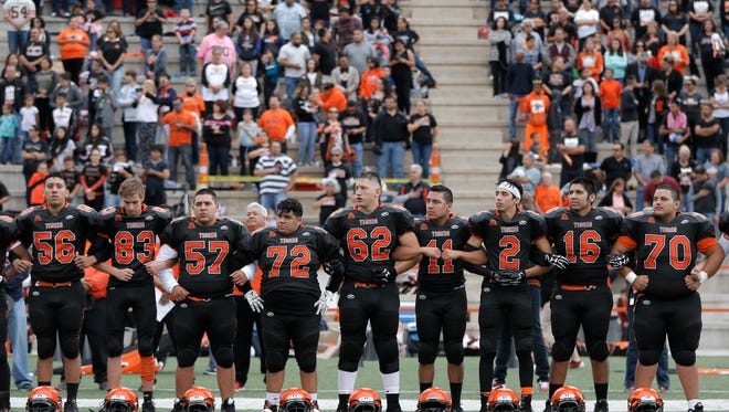 The El Paso High School football team links arms as they listen to the playing of the National Anthem Saturday prior to their game against Austin.