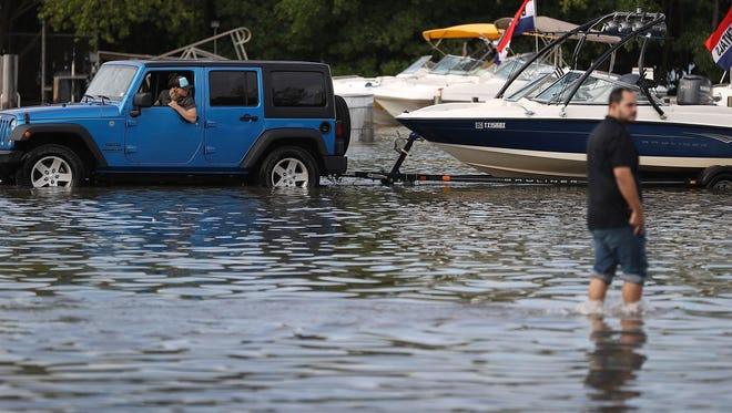 Nick Trace drives through a flooded parking lot to put his boat in at a boat ramp on Nov. 14, 2016, in North Miami, Fla. The flood waters are caused by the combination of the lunar orbit which causes seasonal high tides, also known as a King tide, and what some scientists believe is rising sea levels due to climate change.