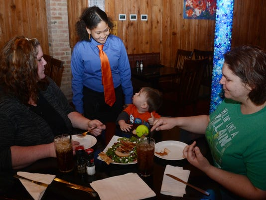 ANI Embers Embers' server Ebony McMillan (second from left) smiles at Lucas Ortego (third from left) as and Aimee Cartwright (left), along his mother Rachal Ortego (far right) enjoy a meal at Embers in downtown Alexandria.-Melinda Martinez/mmartinez@thetow