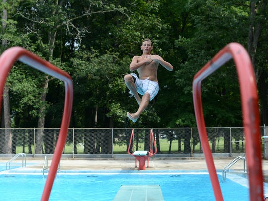 Ian Way, 14, leaps off one of the diving boards Aug.