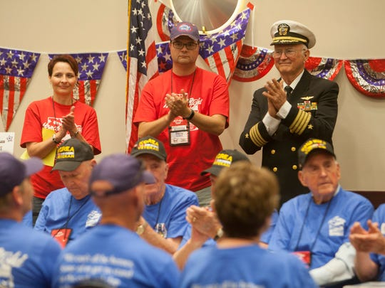 Utah Honor Flight medic Celeste Sorenson, flight leader David Cordero and retired Navy Capt. Ron Lewis applaud during a program welcoming home veterans, guardians and staff on June 16, 2018.