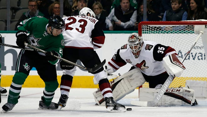 Arizona Coyotes goalie Louis Domingue eyes the puck as Dallas Stars' Antoine Roussel (21) and Arizona Coyotes' Oliver Ekman-Larsson (23) battle in front of the goal during the first period of an NHL hockey game, Friday, Feb. 24, 2017, in Dallas.
