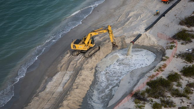 Sand flows through a pipe onto the beach as it is dredged out of Blind Pass on Friday, March 17, 2017, on Sanibel Island.