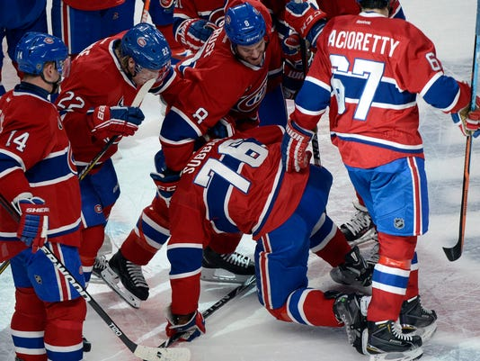 Montreal Canadiens' P.K. Subban (76) is mobbed by teammates after scoring the winning goal in overtime against the Nashville Predators in an NHL hockey game Tuesday, Jan. 20, 2015, in Montreal. Montreal won 2-1. (AP Photo/The Canadian Press, Rayn Remiorz)