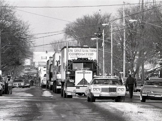 With a police car leading the way, a caravan of 52 trucks loaded with Billy Beer moves through the main intersection of downtown Cold Spring in November 1977 on its way to wholesalers in Minnesota and Wisconsin.