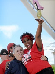 Carlos Gomez, CEO of Western North Carolina Community Health Services, and Valerie Wilson celebrate winning an award for having the most spirited team at Walk a Mile Asheville on Saturday, May 2, 2015.  For a photo gallery from Saturday's event go to Citizen-Times.com