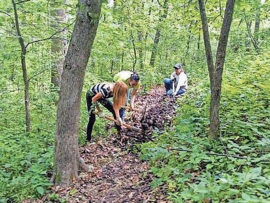 Urban Youth Corps work on a trail through Lake Iowa