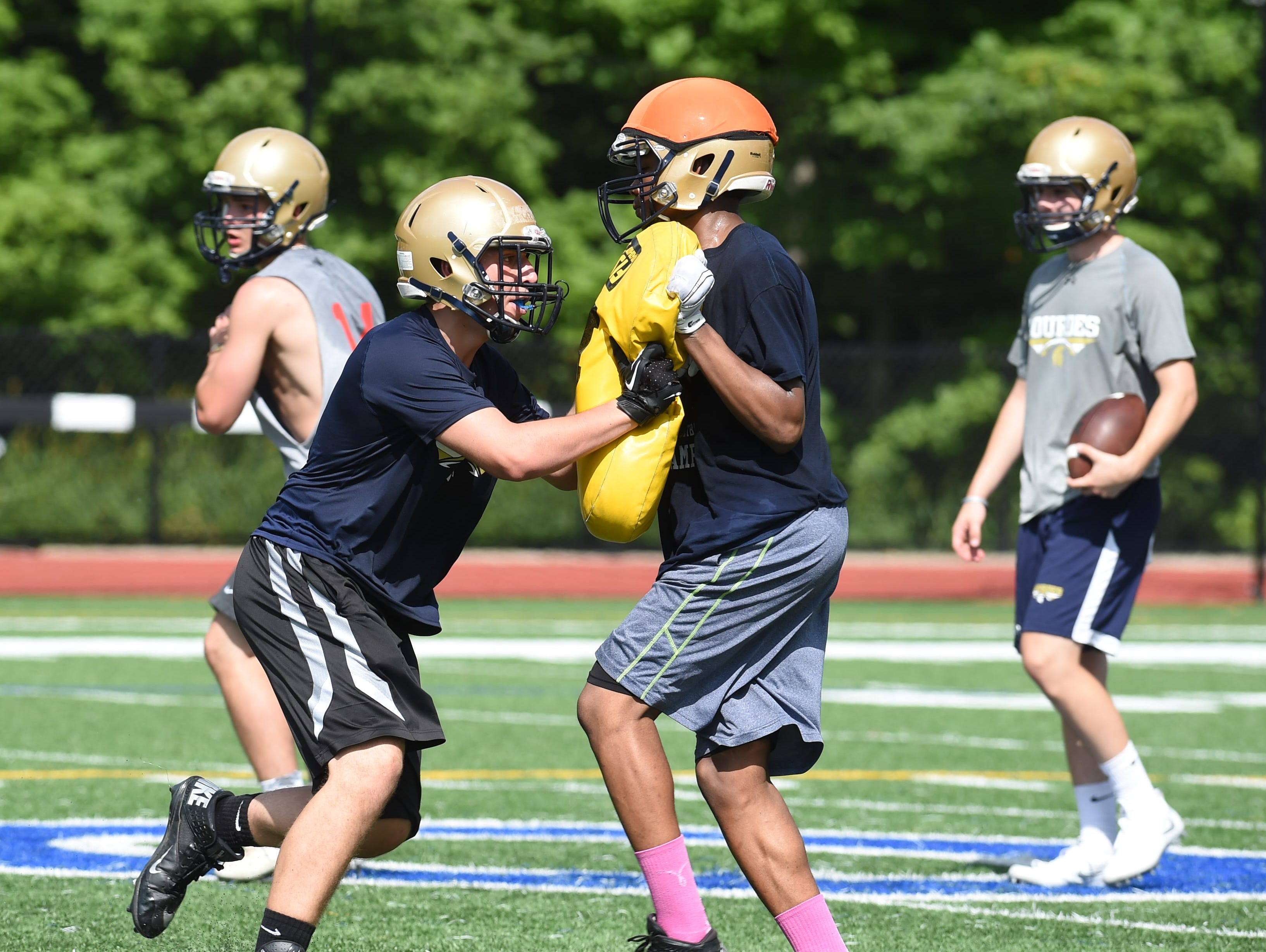 Juniors Sean McDowell, left, and Malik Wright, right, at Our Lady of Lourdes High School grapple during preseason football practice.