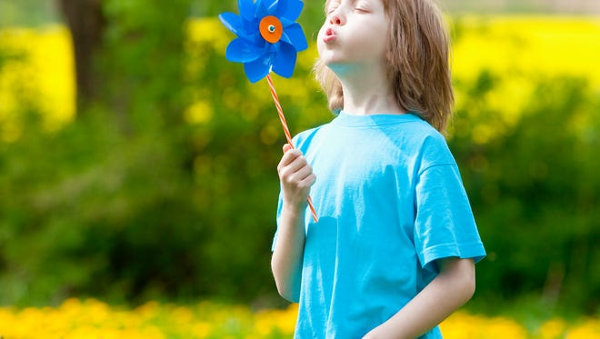 A boy with a blue pinwheel, which represents child abuse prevention. Child abuse cases in Livingston County increased by 56% between 2009-2015.