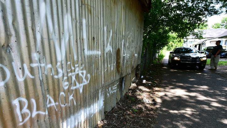 In this July 2016 file photo, Madison County narcotics investigators check out suspected gang-related graffiti on the side of a building July 6 in Canton. A bill before the senate could help add enhanced penalties to crimes committed by validated gang members, and Gov. Phil Bryant and others say it's a major strike in the fight against violent crime in the Magnolia state.
