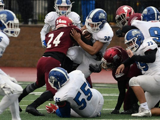 Harper Creek RB Jalonty Hervey (32) tries to push through a pile of Muskegon defenders Saturday afternoon.