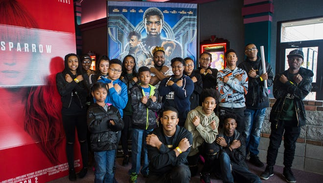 """Timothy Green, Jr., wearing a crown, poses for a portrait with a group of youths as they do the Wakanda salute at Malco Stage Cinema after screening """"Black Panther"""" in Bartlett on Feb. 17, 2018."""