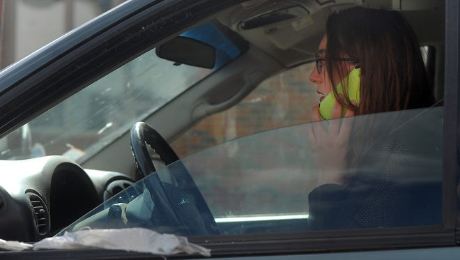 A motorist talks on her cell phone while driving along Minnesota Ave. and 26th Street on Thursday, May 21, 2015.