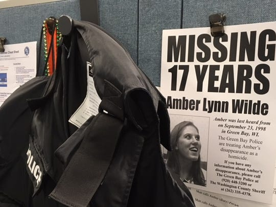 "Amber Wilde's ""missing"" poster hangs next to a bullet-resistant vest on a Green Bay police detective's wall."