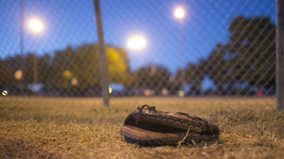 1110121500mm PNI1116-mr guerrero --11/12/12-- A baseball glove sits on the ground at the end of practice underneath one of the few lights on the edge of Guerrero Rotary Park in Phoenix, AZ on November 12, 2012. The Little League Rattlers play at the park, but have to head in early because there are no lights there.  Patrick Breen/ The Republic