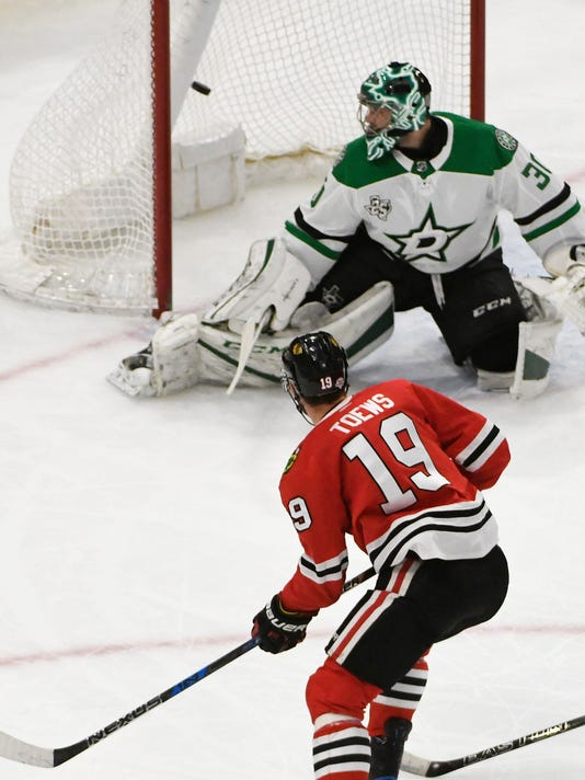 Chicago Blackhawks center Jonathan Toews (19) scores a goal on Dallas Stars goaltender Ben Bishop (30) during the first period of an NHL hockey game Thursday, Feb. 8, 2018, in Chicago. (AP Photo/David Banks)
