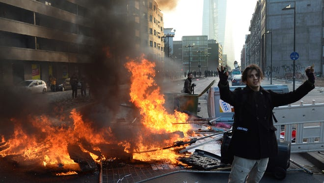 A demonstrator stands in front of the European Central Bank next to a burning barrier in Frankfurt on March 18, 2015.