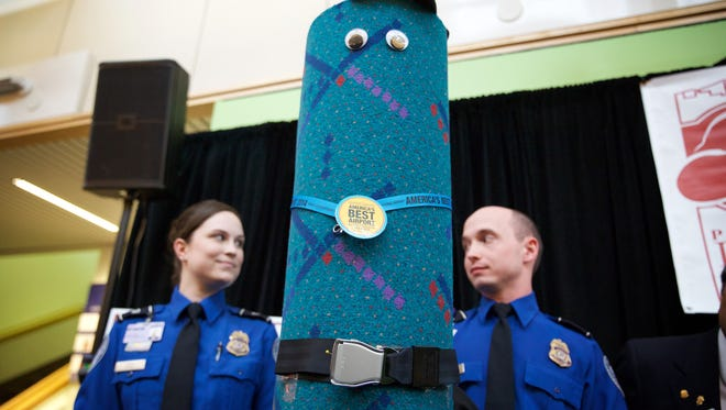 TSA officers Andrea Green, left,  and Edmund Gray stand beside a piece of dressed up old carpet from the terminal at Portland International Airport during a press conference on March 20, 2015.