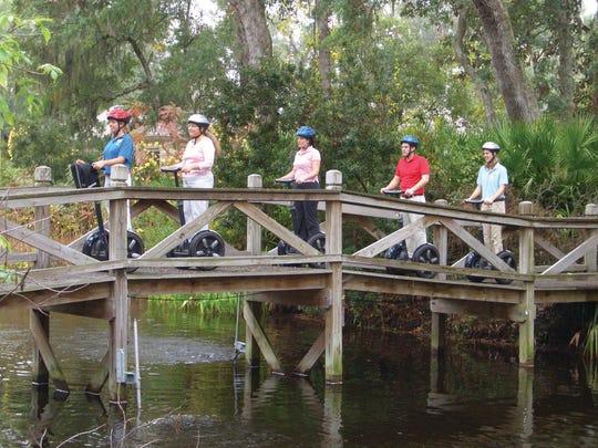 A Segway tour passes over a bridge at Omni Amelia Island Plantation.