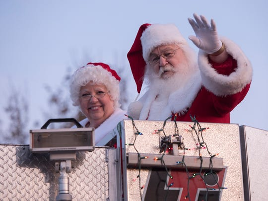 Santa and Mrs Claus ride it the bucket of the Livonia Fire Department's aerial truck.
