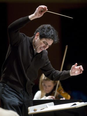 """DSO Music Director David Amado in rehearsal. He'll lead the symphony in two performances of """"Heaven and Earth"""" this weekend."""