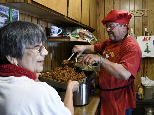 Ron Subia fills a pan held by friend Toni Harris with