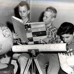 Audubon High School students (from left) Bill Walker, Douglas Smith and Vince Baldino look over an astronomy book.