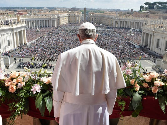 FILE - In this April 16, 2017, file photo, Pope Francis addresses the crowd from the main balcony of St. Peter's Basilica, at the Vatican. Jim Harbaugh's latest, outside-the-box idea is about to take off. Michigan's football team will travel to Rome this weekend and will kick off the unique trip by meeting with refugees before going to the Vatican for a Papal address and practicing a few times. (L'Osservatore Romano/Pool Photo via AP, File)