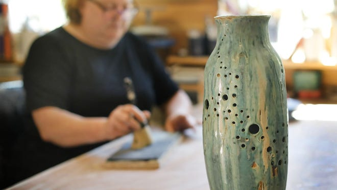Michelle Green at work in her Hinhgam studio, near an elegant vase she made.