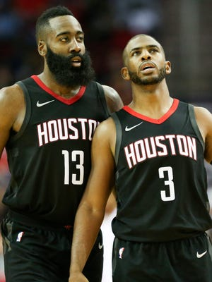 Houston Rockets guard Chris Paul (3) and guard James Harden talk during a timeout during the second half of a game against Brooklyn.