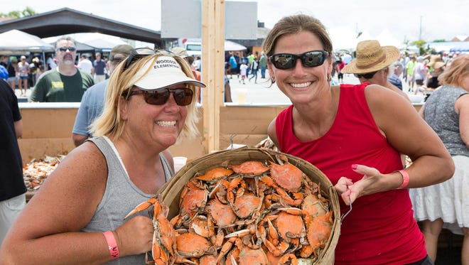 Kim Swann, of Crisfield, and Courtney Monar, of Salisbury, pose for a photo holding a bucket of steamed crabs.